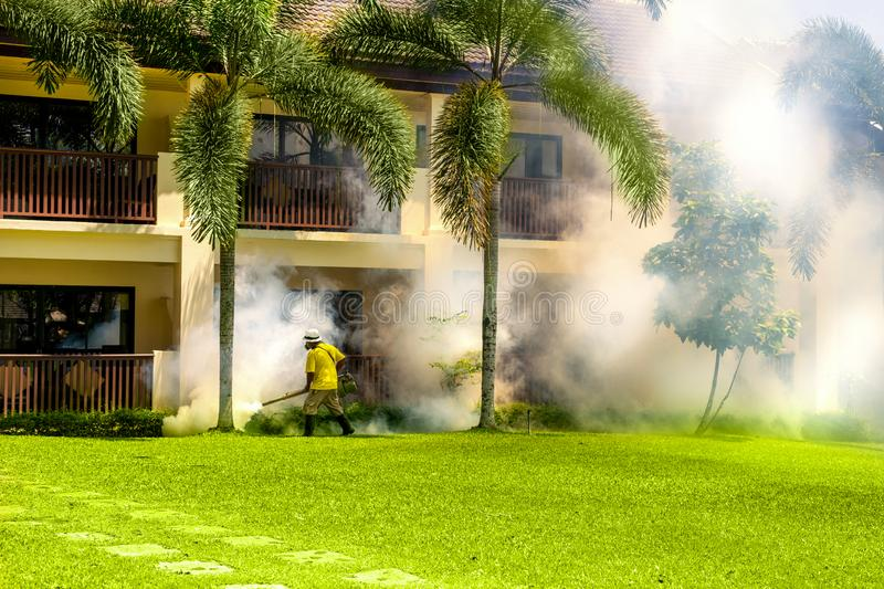 A gardener doing a poisoning activities by spraying insecticide or pesticides to control the insects in hotel. Thailand.  stock photo