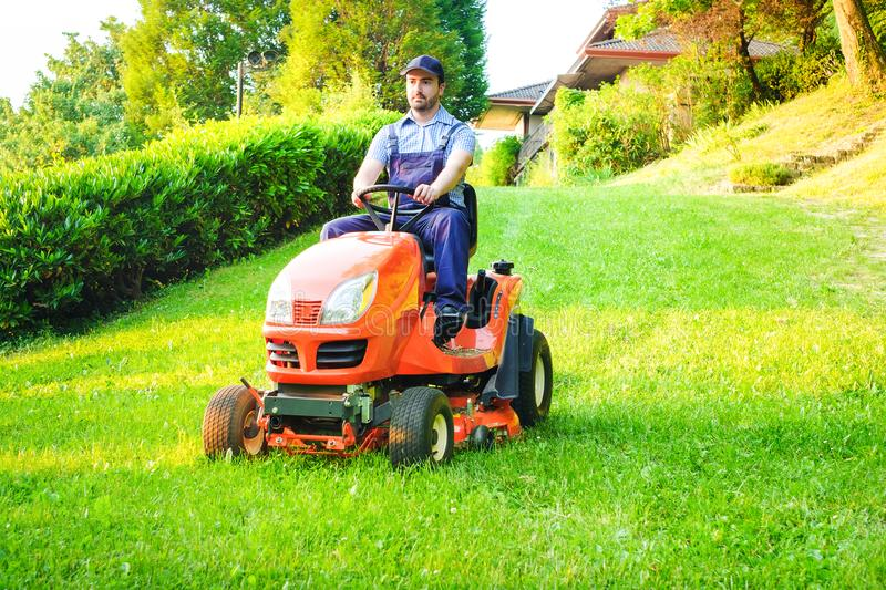 Gardener driving a riding lawn mower in garden. Gardener driving a riding lawn mower in a garden stock photo