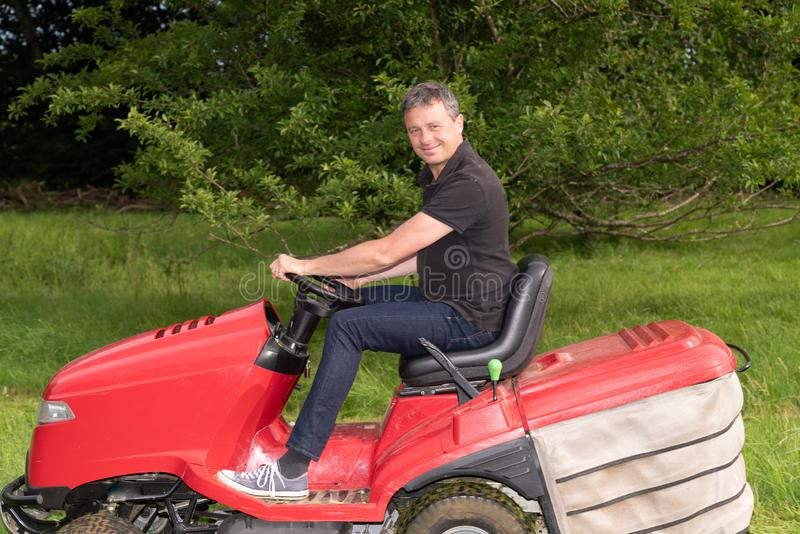 Gardener driving riding lawn mower in garden royalty free stock photography