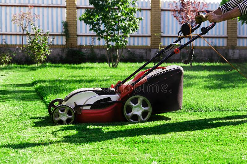 Gardener by electric lawn mower cutting green grass in the garden. Garden meadow lawn cutting. Worker guy trimmed grass field. stock image
