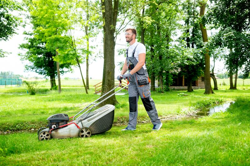 Gardener equipped with lawnmower on the job. Concept of lawn mowing stock images
