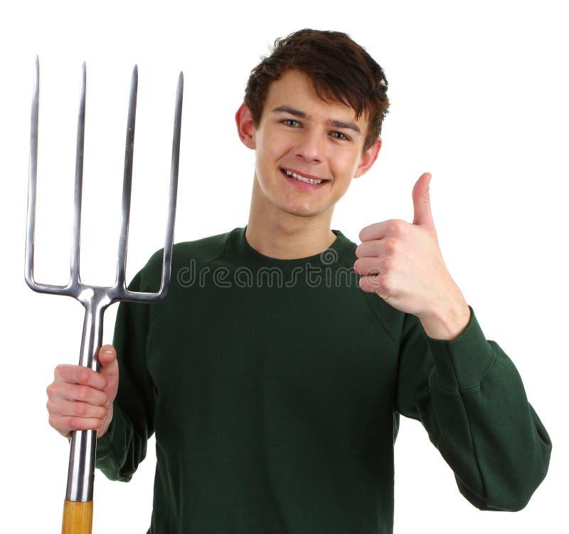 Gardener with a fork. A gardener with a fork and a thumbs up sign stock photos