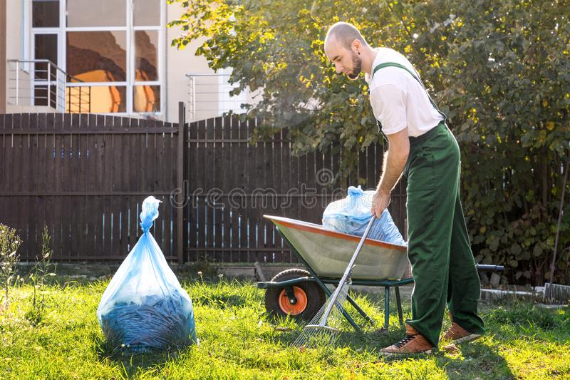 The gardener in the green uniform is cleaning the yard.On the grass is a cart with compost and a package of garbage royalty free stock image