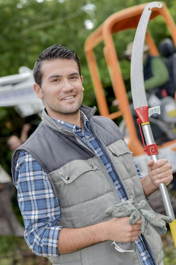 Gardener holding gloves and pruning saw stock image