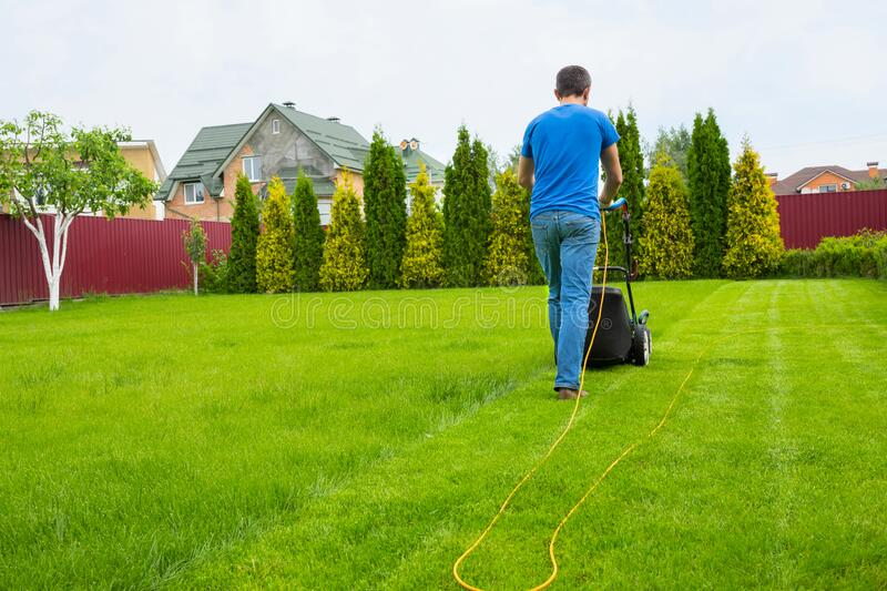 A gardener with a lawn mower is cutting grass in the garden in the house backyard stock images
