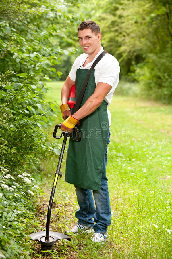 Gardener with lawn trimmer. Young and smiling gardener with lawn trimmer stock images