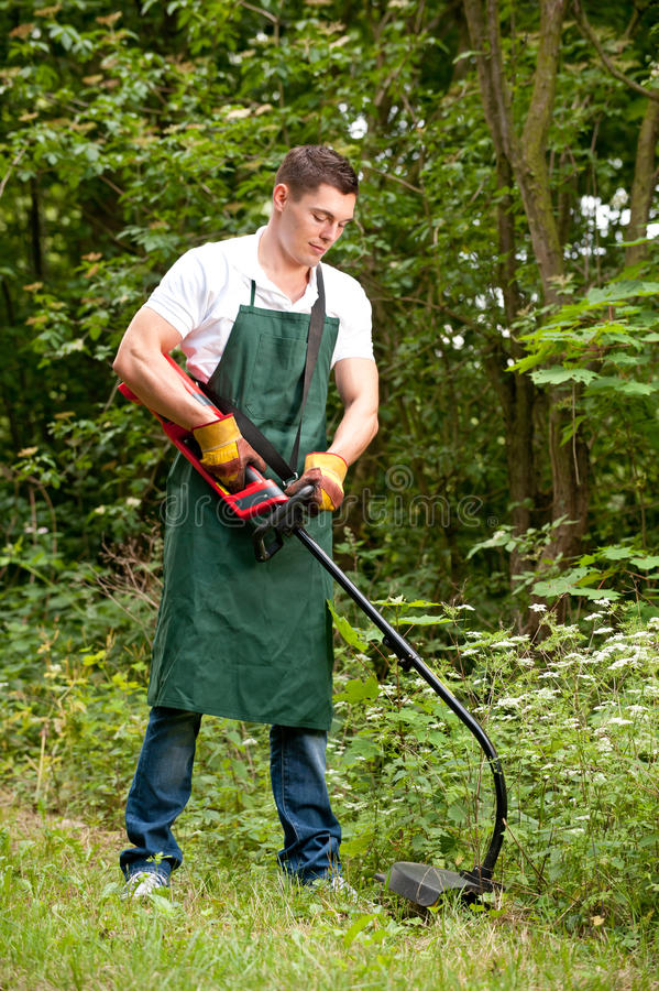 Gardener with lawn trimmer. Young and smiling gardener with lawn trimmer stock photography