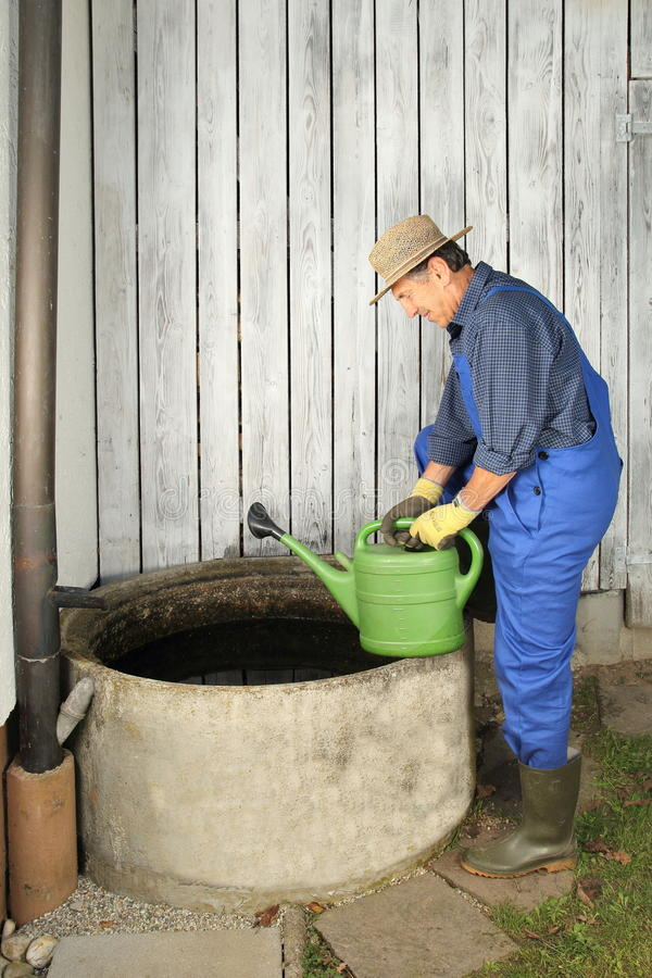 Gardener next to his Rain water barrel. A Gardener next to his Rain water barrel stock images