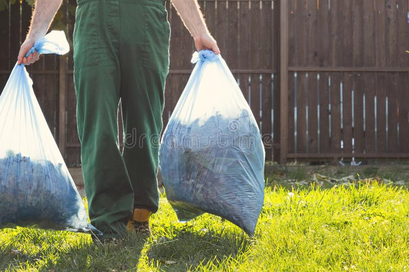 The gardener removes the bags of compost. Light. Green uniform. Close up royalty free stock images
