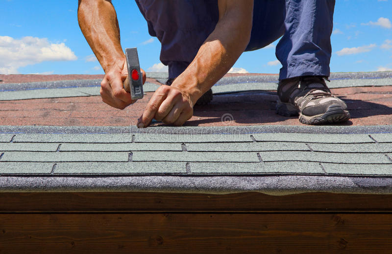 Gardener renew roof of summer garden house. With tar paper shingles royalty free stock photos