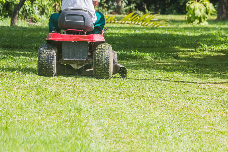 The gardener is using a lawn mower stock photos