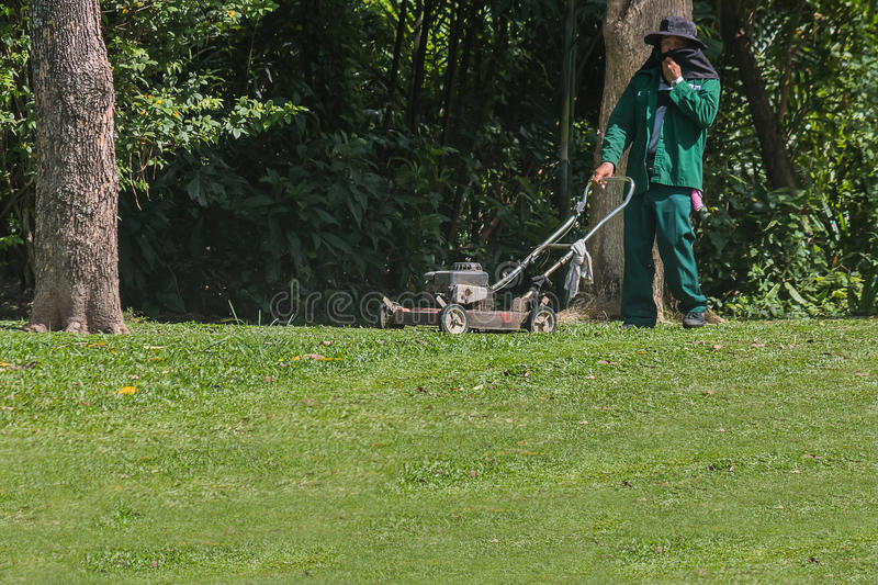The gardener is using a lawn mower stock photo
