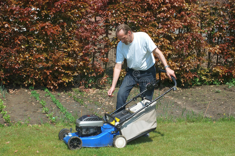 Gardening. Handsome Middle aged man working in the garden with lawnmower stock images