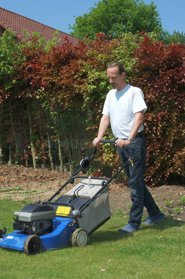 Gardening. Handsome Middle aged man working in the garden with lawnmower royalty free stock images