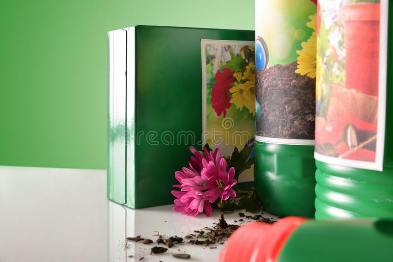 Gardening bottles and containers of products on white table close up. Bottles and containers of gardening products for the growth of plants on white table. With stock photo