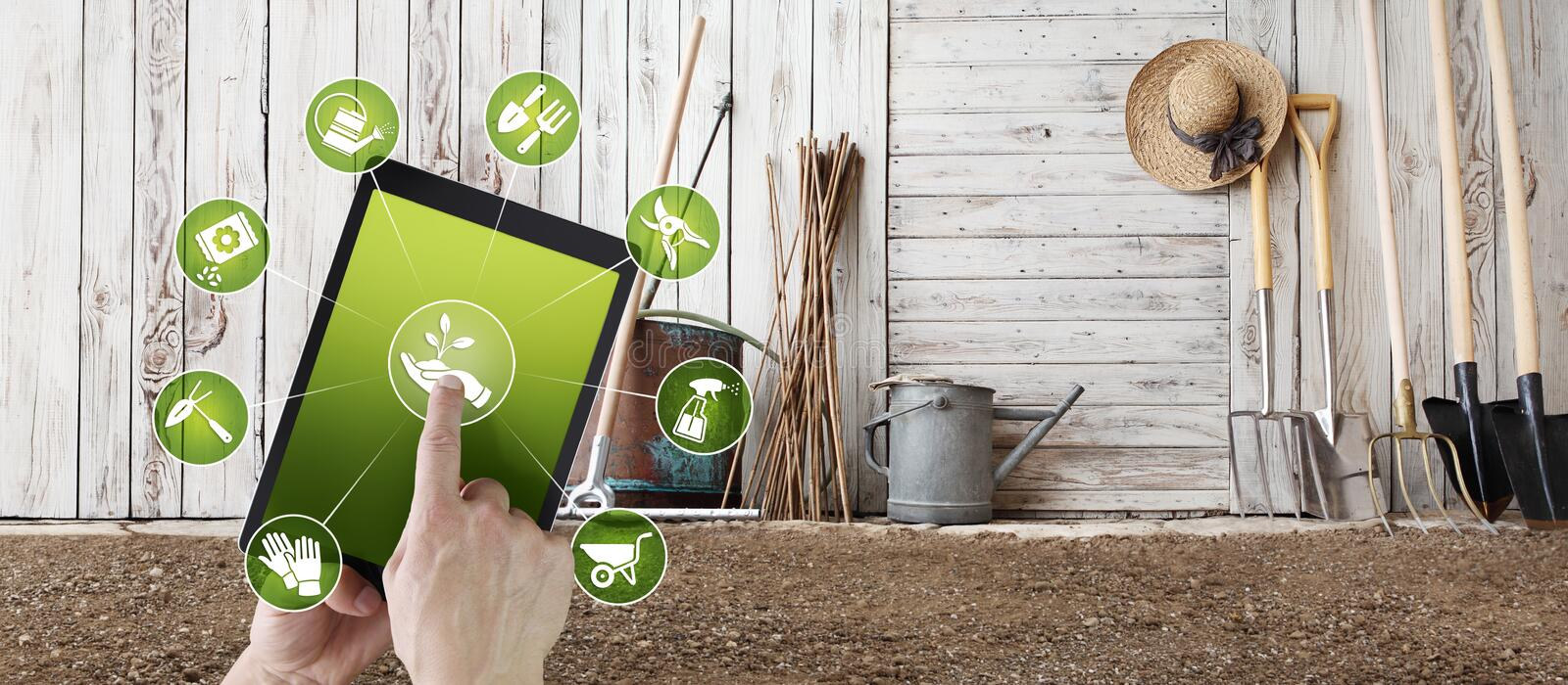Gardening equipment e-commerce concept, online shopping on digital tablet, hand pointing and touch screen with garden tools icons. Tool shed in the background royalty free stock photo