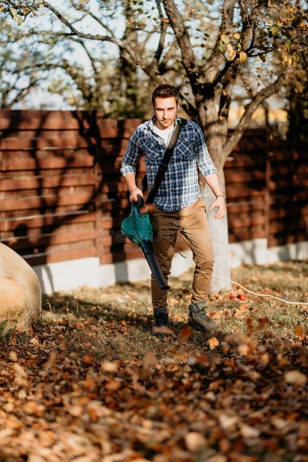 Gardening industry, worker using leaf blower machine stock photos