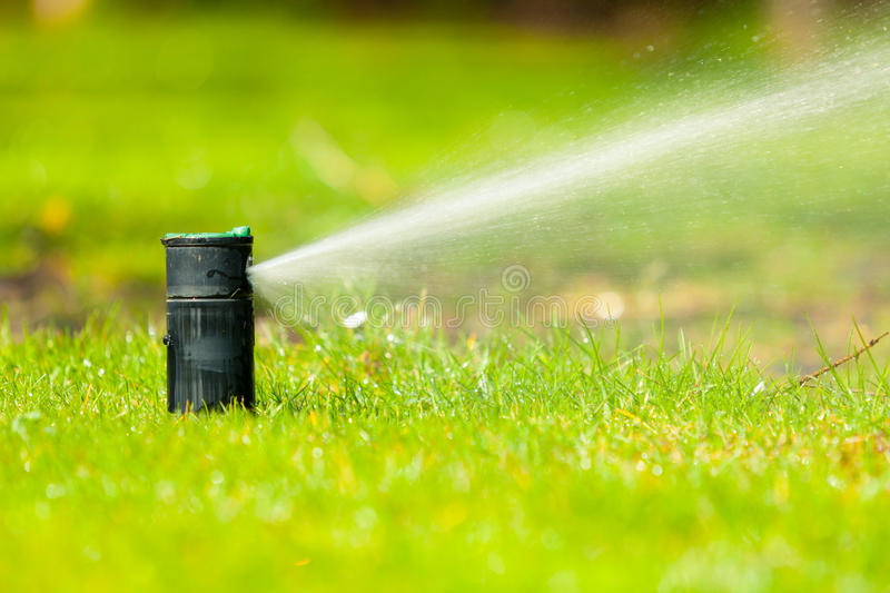Gardening. Lawn sprinkler spraying water over grass. Gardening. Lawn sprinkler spraying water over green grass. Irrigation system - technique of watering in the stock photography