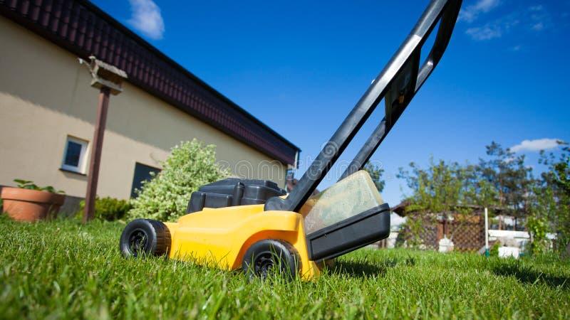 gardening Mähender Rasen mit gelbem Rasenmäher lizenzfreie stockbilder