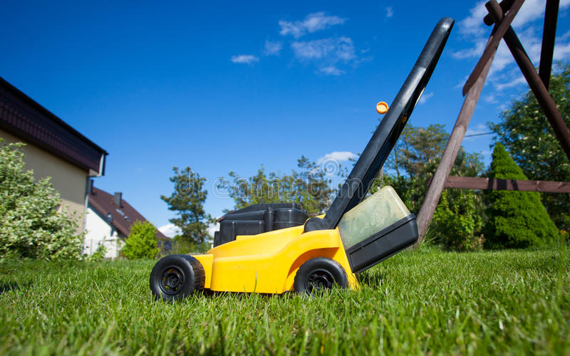 gardening Mähender Rasen mit gelbem Rasenmäher stockfotos