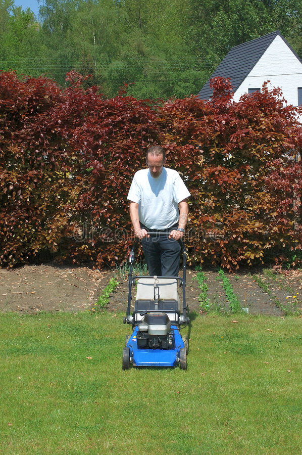 Gardening, mowing the lawn. Handsome Middle aged man working in the garden with lawnmower royalty free stock photography