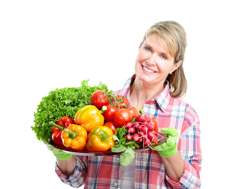 Gardening. Senior woman with vegetables. Isolated over white background stock photos
