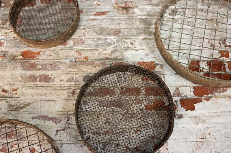 Gardening sieves hanging on a wall. Four vintage metal gardening sieves or riddles hanging on a white washed red brick wall stock images