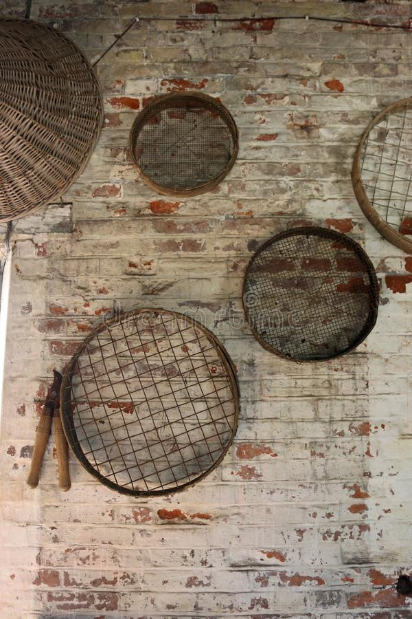 Gardening sieves hanging on a wall. Four vintage metal gardening sieves or riddles hanging on a white washed red brick wall with loppers and a wicker basket stock photo