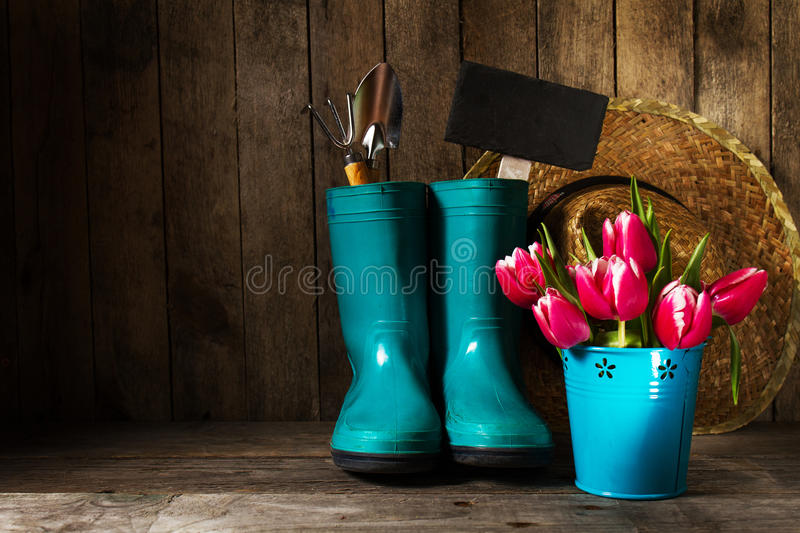 Gardening tools with blue rubber boots, straw hat, spring flower stock images