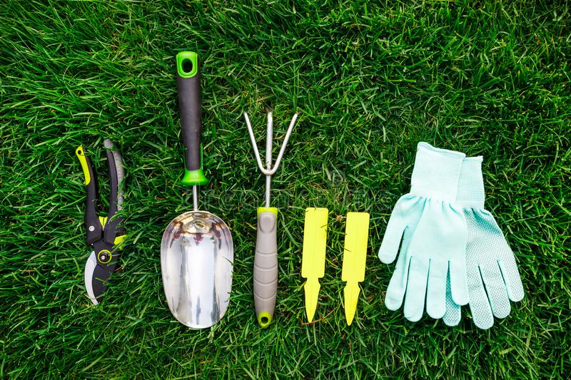 Gardening tools and equipment close up on the green grass, garden maintenance and hobby concept royalty free stock photos