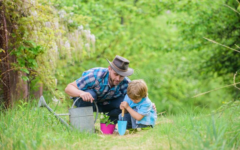 Gardening tools. Planting flowers. Dad teaching little son care plants. Little helper in garden. Make planet greener. Growing plants. Take care of plants. Boy stock image