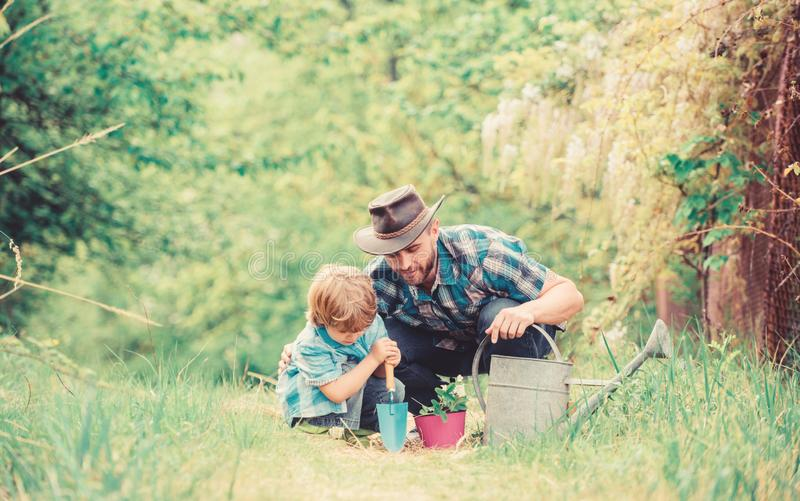Gardening tools. Planting flowers. Dad teaching little son care plants. Little helper in garden. Make planet greener. Growing plants. Take care of plants. Boy stock images