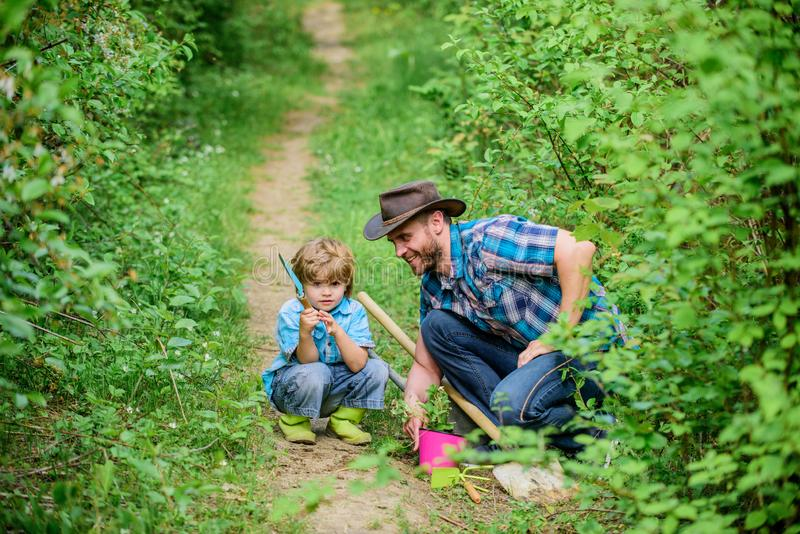 Gardening tools. Planting flowers. Dad teaching little son care plants. Little helper in garden. Make planet greener. Growing plants. Take care of plants. Day stock photo