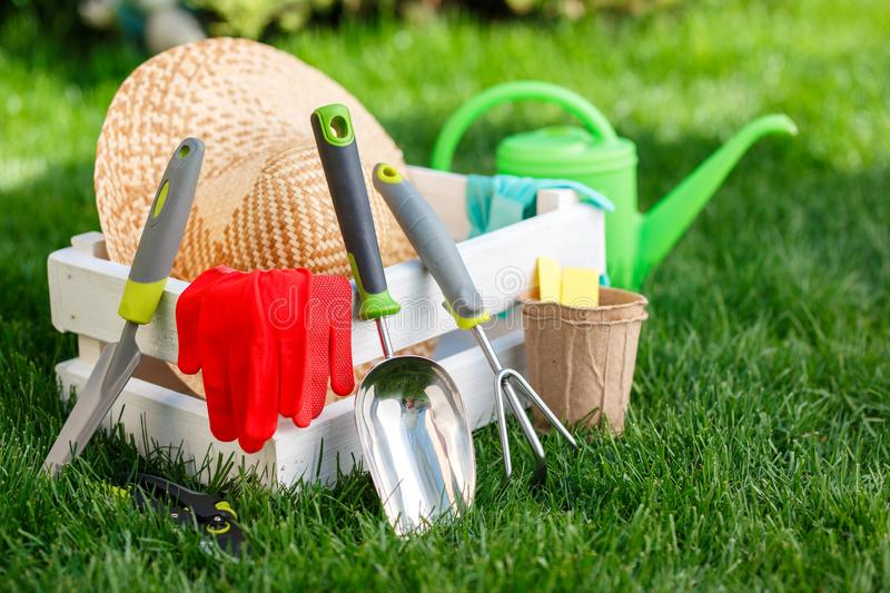 Gardening tools and utensils on green meadow, garden manteinance and hobby concept royalty free stock photos