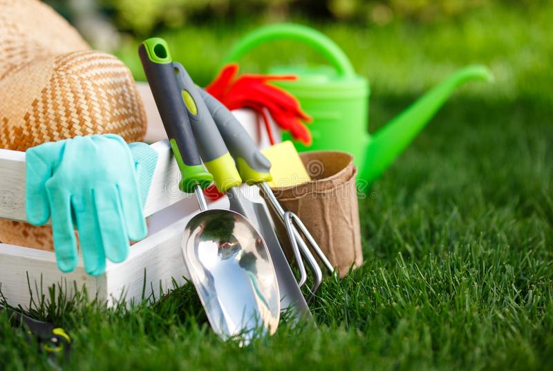 Gardening tools and utensils on green meadow, garden manteinance and hobby concept royalty free stock images