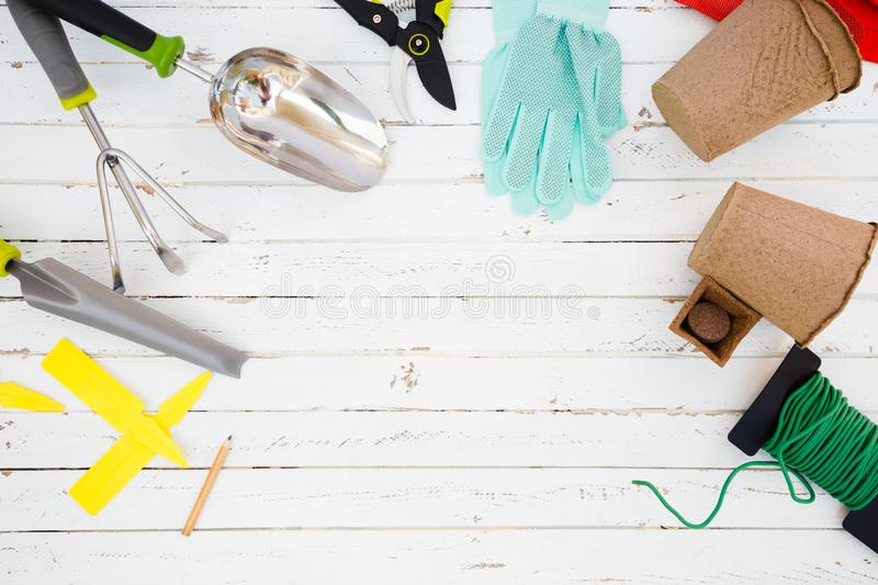 Gardening tools and utensils on white wood table, garden manteinance and hobby concept stock photos