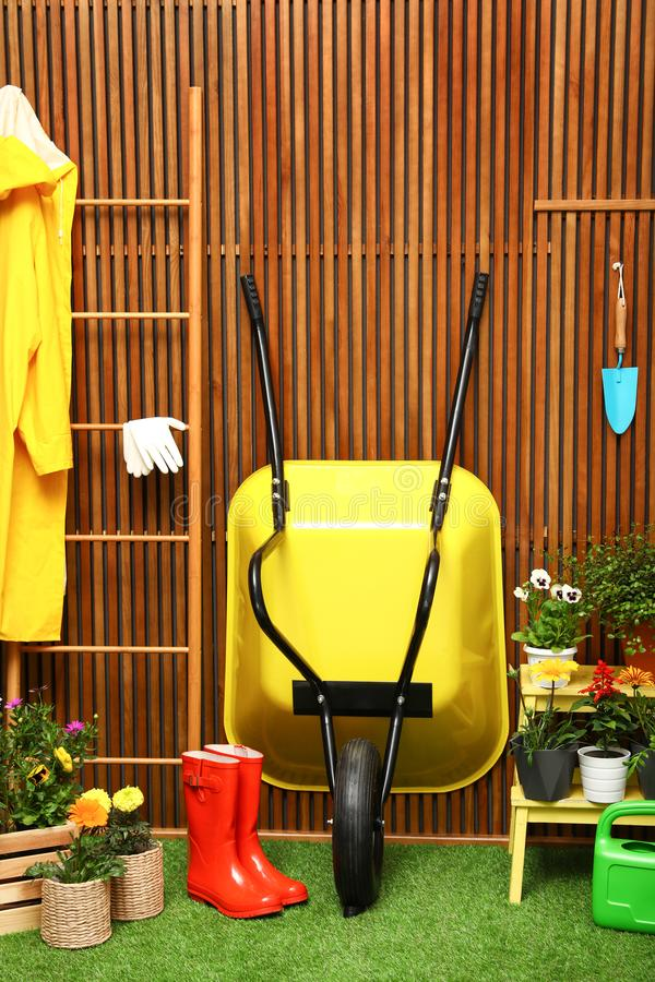 Gardening tools with wheelbarrow and flowers. Near wooden wall stock photography