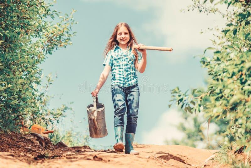 Gardening voor beginners Tips voor tuinieren Veertuinbouw Meisjeskind kan schoppenwater vasthouden Veertuinbouw stock foto