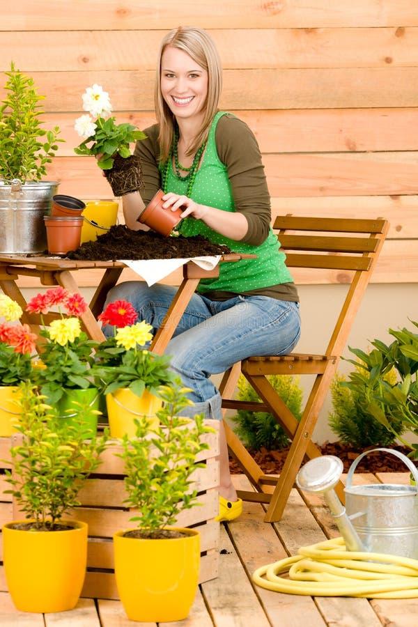 Gardening woman plant spring flower terrace. Gardening woman hold flowerpot plant spring terrace stock photo