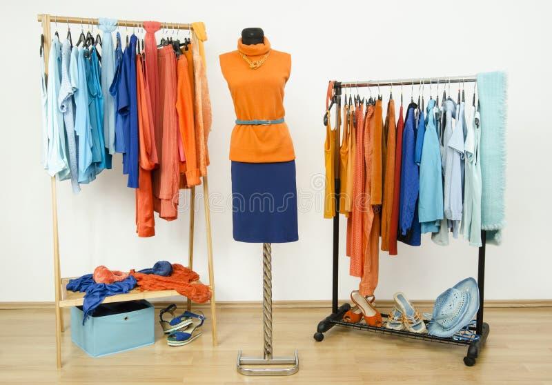 Garderoba z uzupełniającymi kolorami pomarańcze i błękitów ubraniami układał na wieszakach fotografia stock