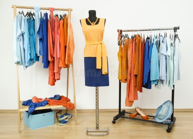 Garderoba z uzupełniającymi kolorami pomarańcze i błękitów ubraniami układał na wieszakach obraz stock