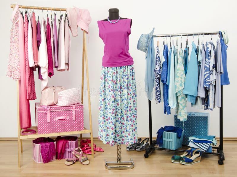 Garderoba z z menchiami i błękitów ubraniami układał na wieszakach Śliczny lato strój na mannequin obraz stock