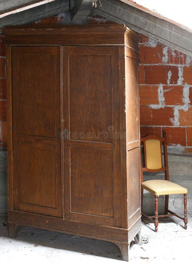 Garderobe in de stoffige zolder van oud Huis en een oude stoel royalty-vrije stock afbeeldingen