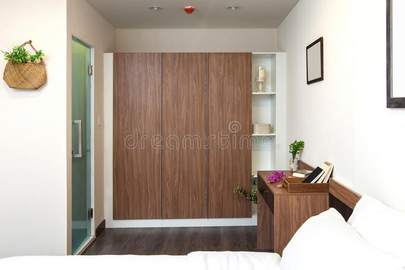 Garderobe eingebaut und Schreibtisch hölzern auf Schlafzimmer mit Toilette herein lizenzfreies stockbild