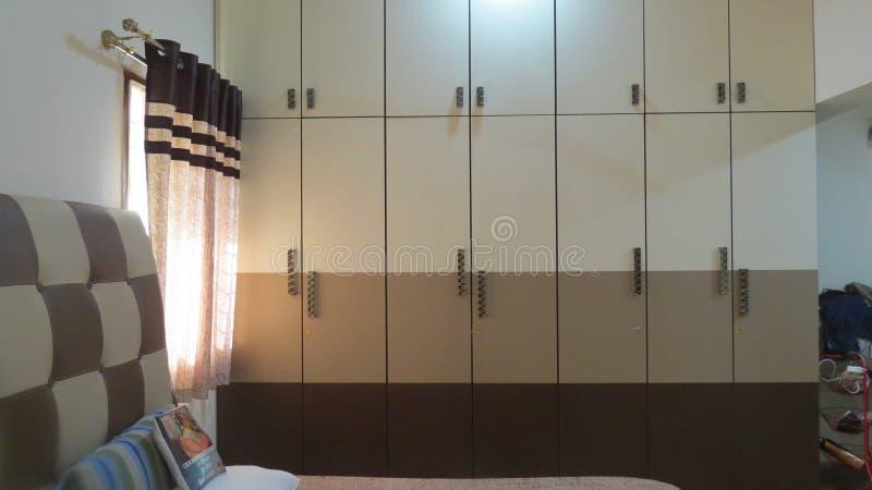 Garderobmöblemang i sängrum med hög löneförhöjning för säng arkivfoto