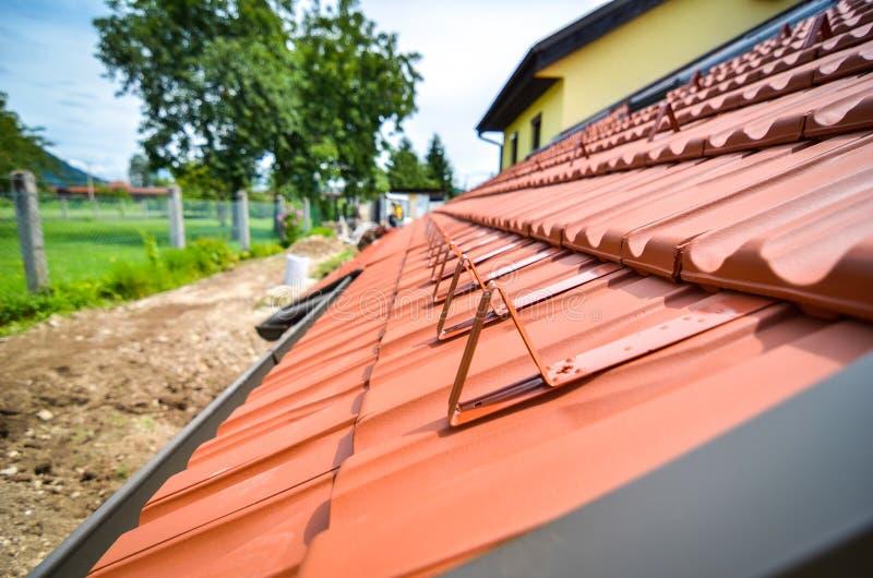 Gardes de neige sur de nouvelles tuiles de toit image libre de droits