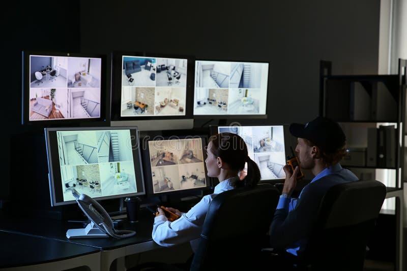 Gardes de sécurité surveillant les caméras modernes de télévision en circuit fermé dans la chambre de surveillance images stock