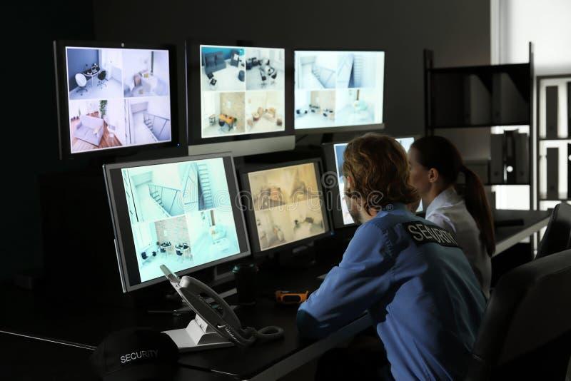 Gardes de sécurité surveillant les caméras modernes de télévision en circuit fermé dans la chambre de surveillance photos stock