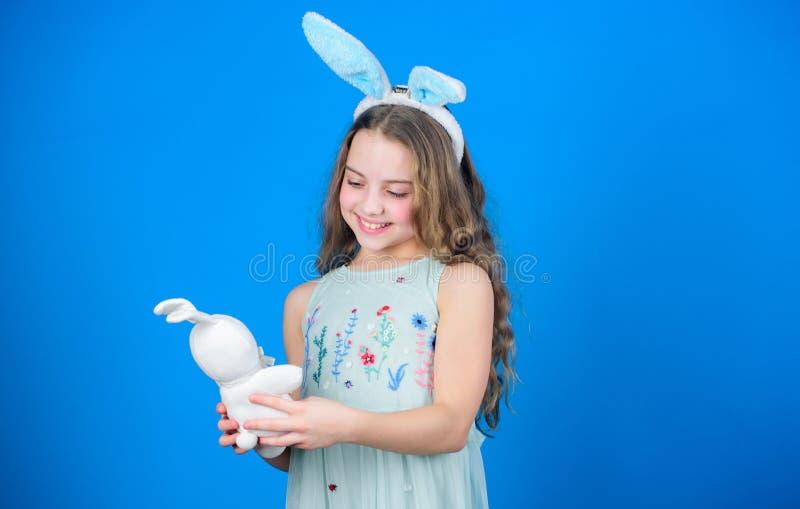 Gardez Pâques calmes et Joyeuses Peu jouet de fille et de lapin Petite fille dans des oreilles de lapin avec le jouet de Pâques p photo stock