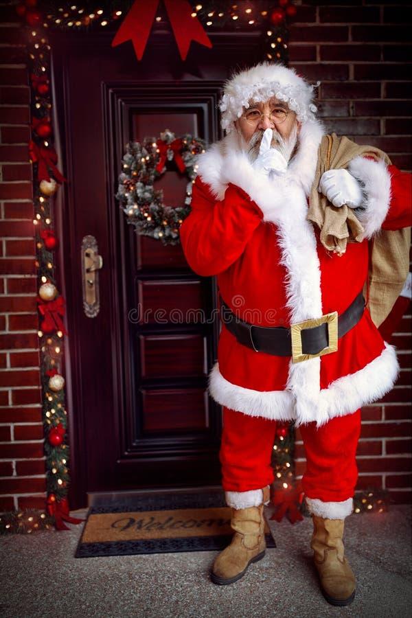 Gardez Santa Claus secrète arrive avec le cadeau de Noël photographie stock